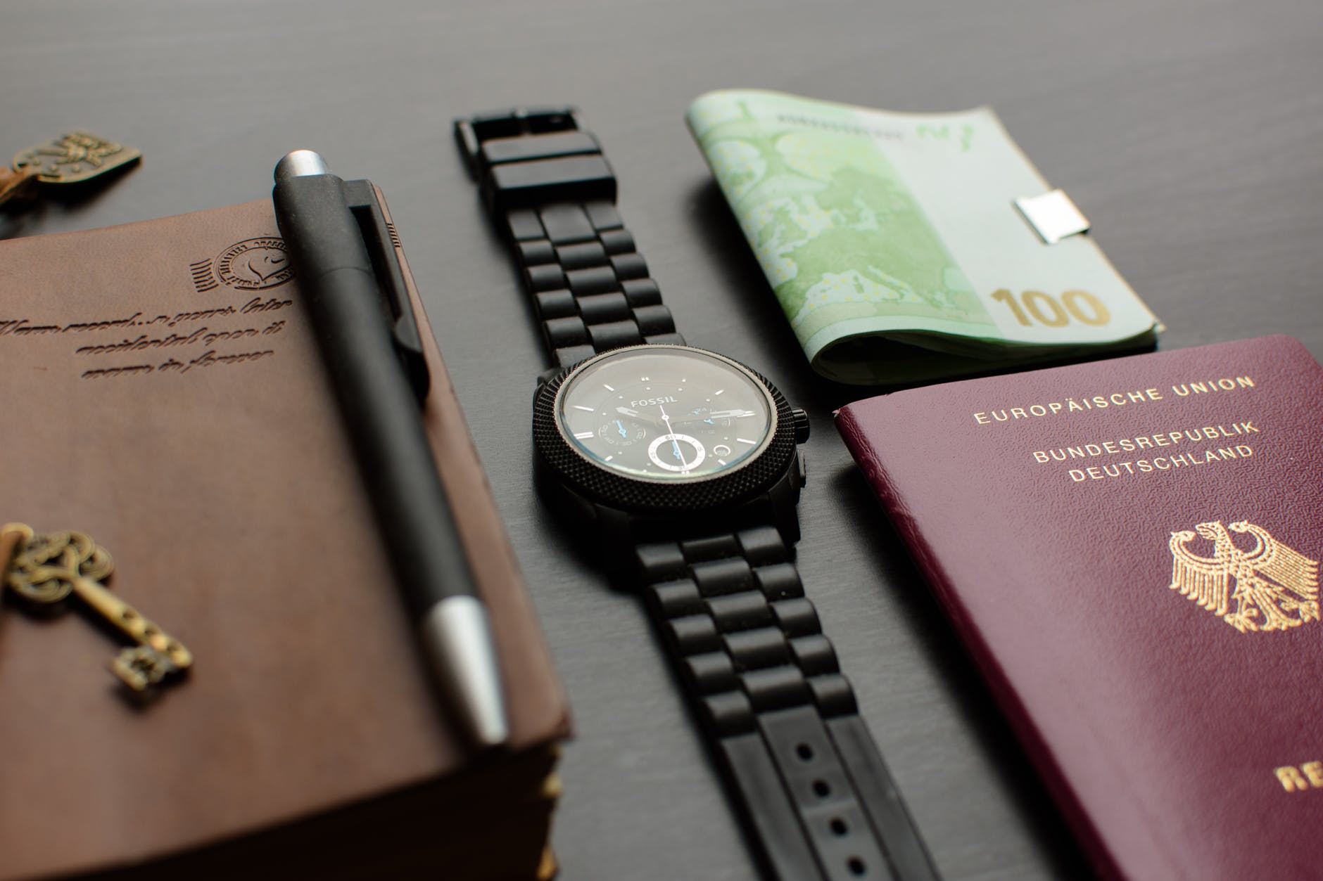 round black chronograph watch on table near germany passport an banknote on table