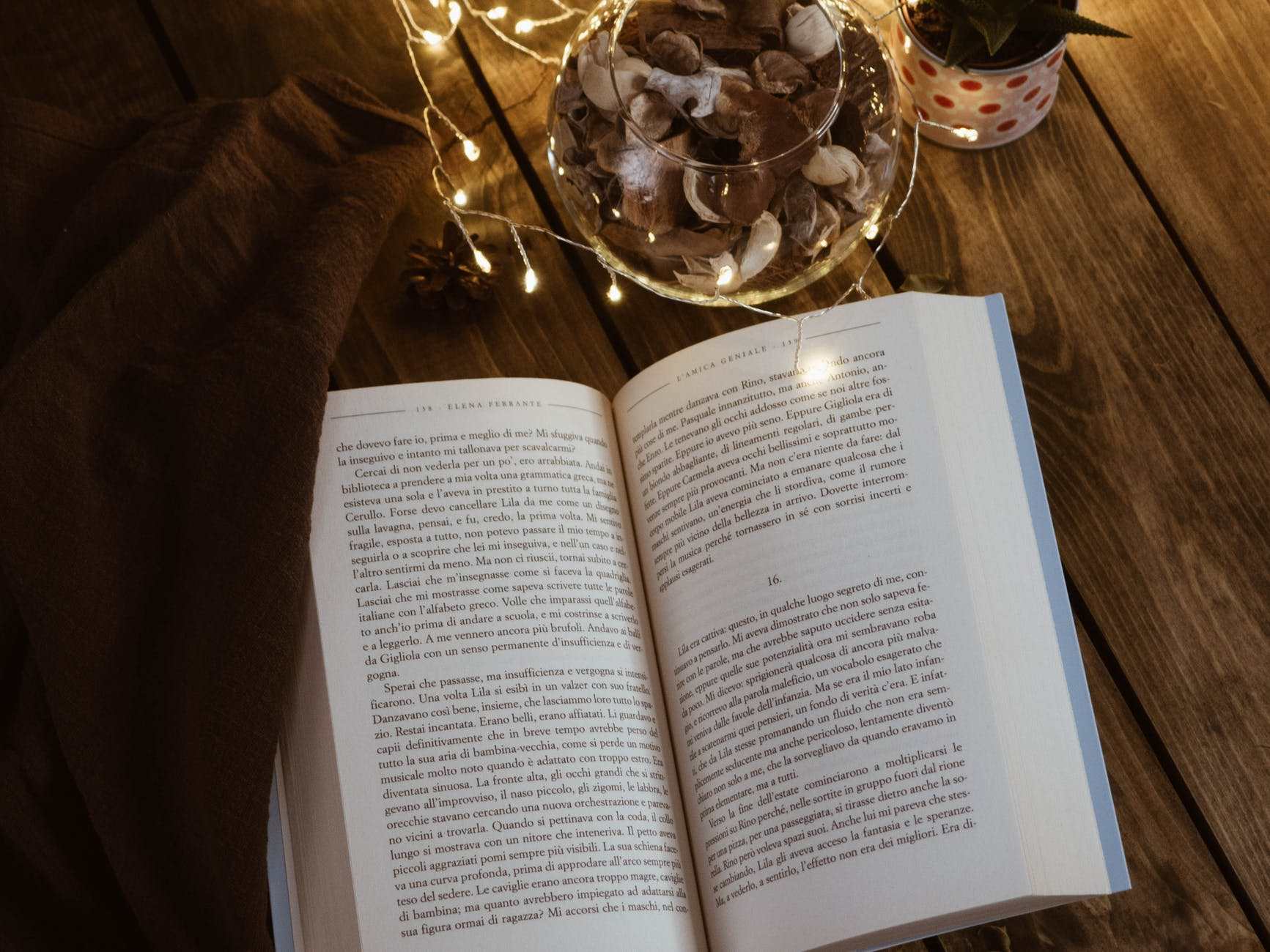open book and fairy lights on wooden surface