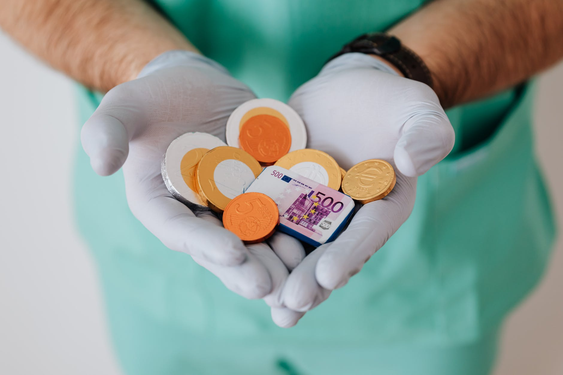 faceless doctor with chocolate coins in hands