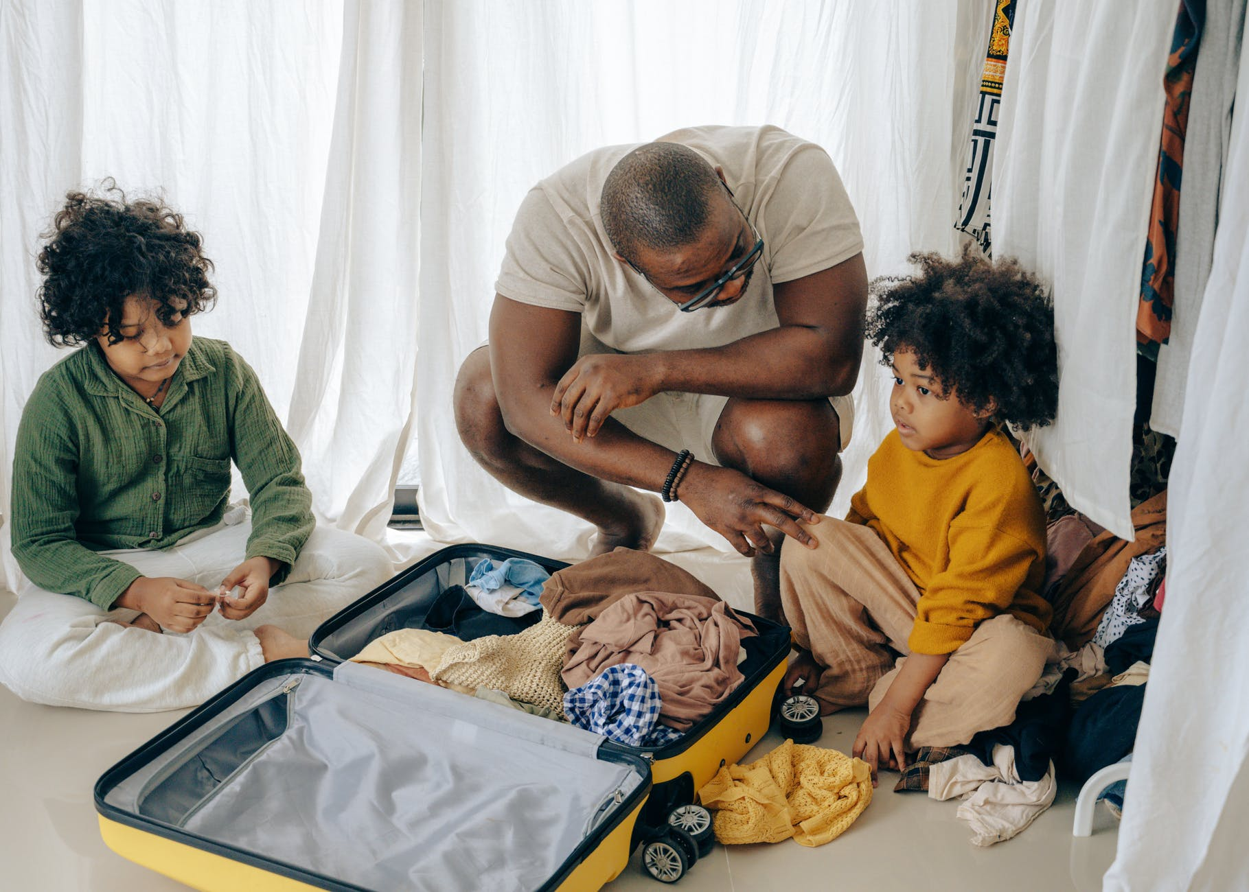 african american father with kids sitting near suitcase